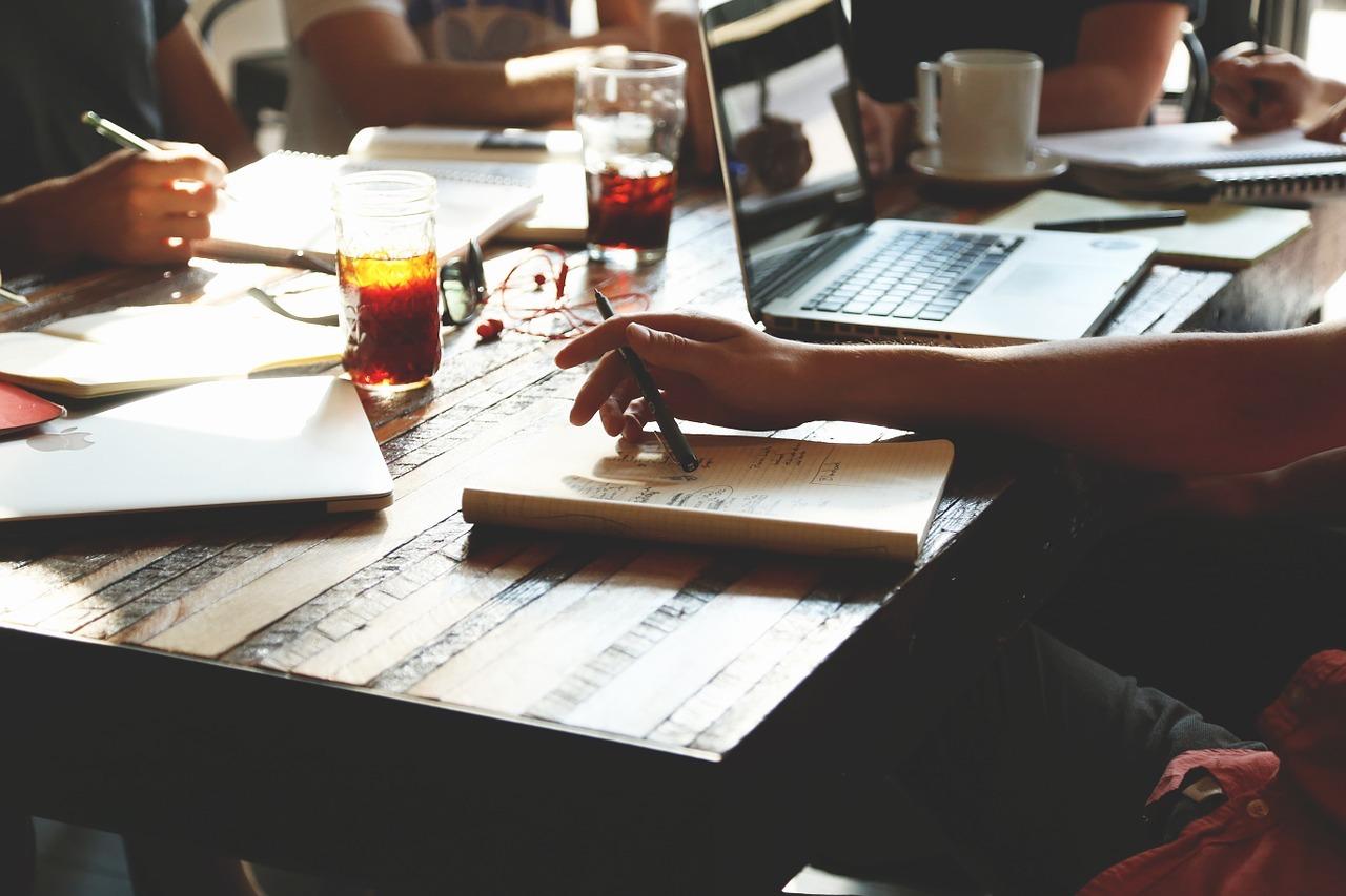 scrivania. persone. lavoro. bicchieri. computer. penne. appunti.